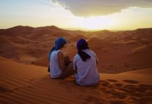 a man and woman admiring sunset in moroccan desert