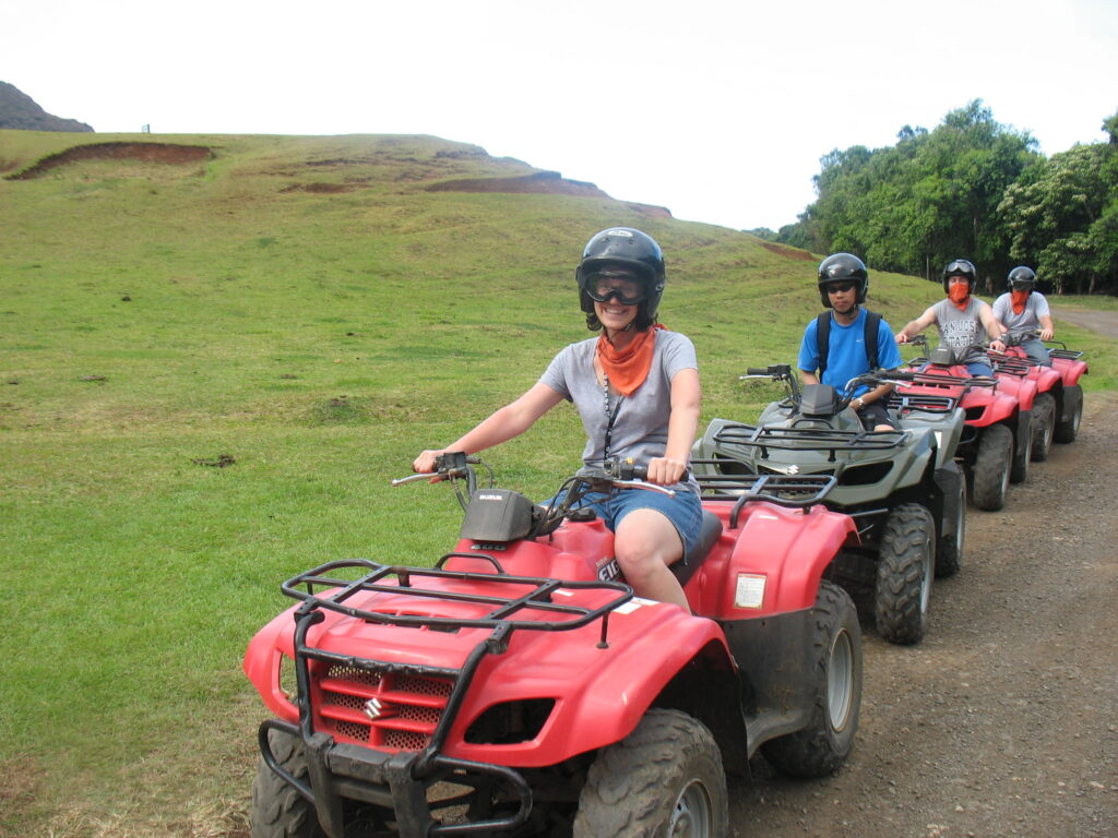 Four people riding ATVs with Godzilla's giant footprints at Kualoa Ranch as backdrop