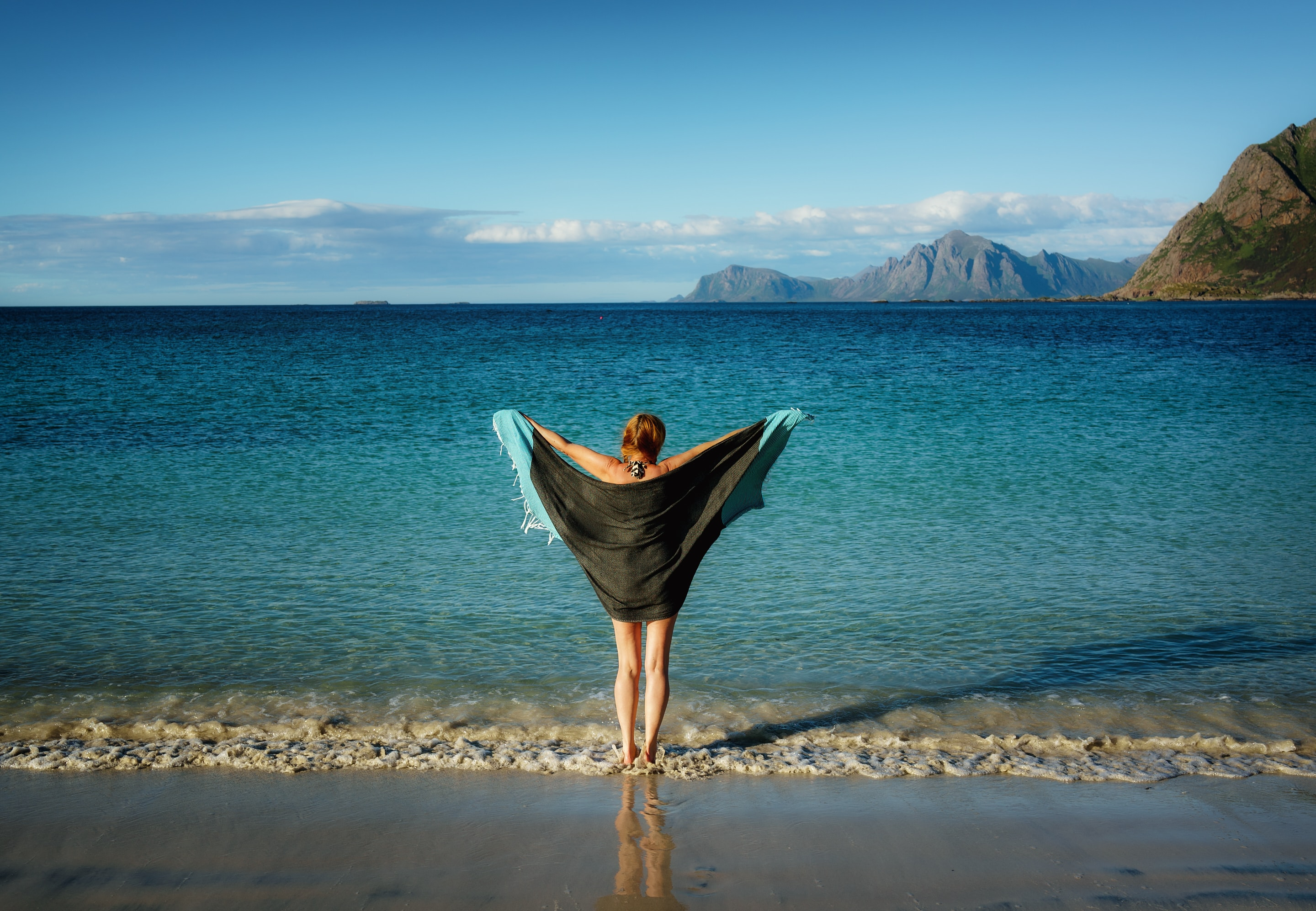 A woman holding a beach towel facing the beach