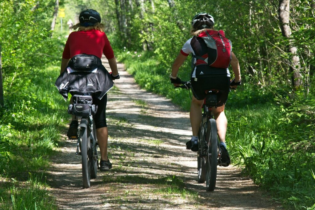 Two people riding a bike in the woods.