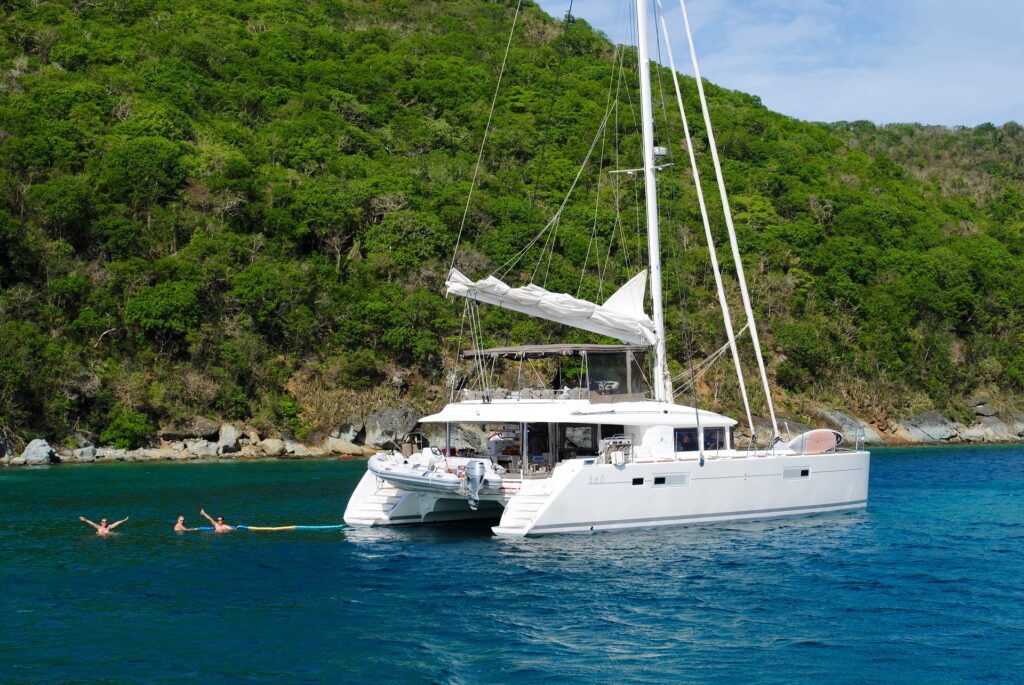 A catamaran docked in open sea in front of an islet.