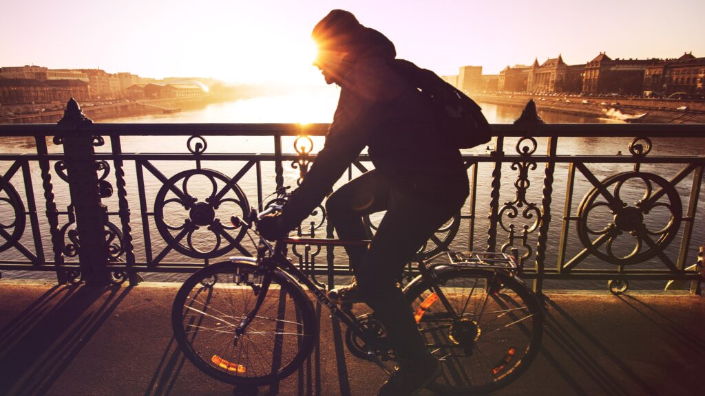 A man biking under sunset.