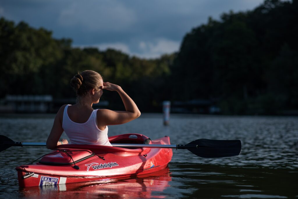 A woman riding on a kayak in an open water.