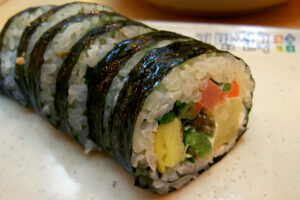 A roll of kimbap with vegetables and egg fillings.