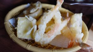 A serving of twigims or deep friend shrimp with potato batter.