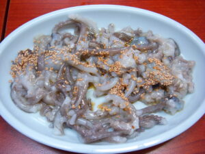 A plat of small live octopus topped with sesame seeds and chilli oil.