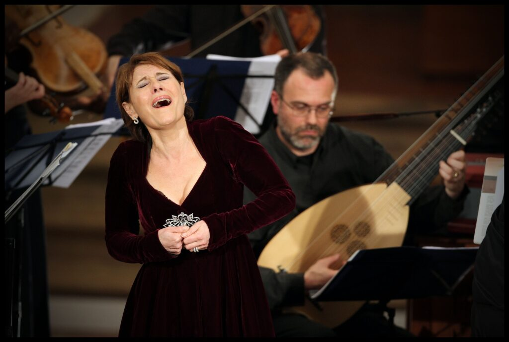 A woman in red velvet gown singing alongside an orchestra.