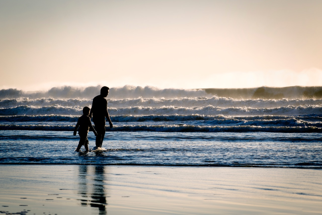 father and son playing at Pismo beach with heavy crashing waves