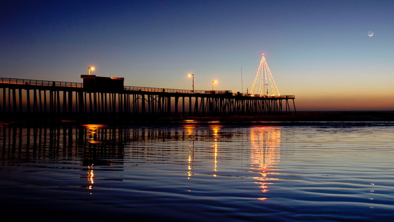 Silhouette of waves under the lighted bridge of Pismo Pier