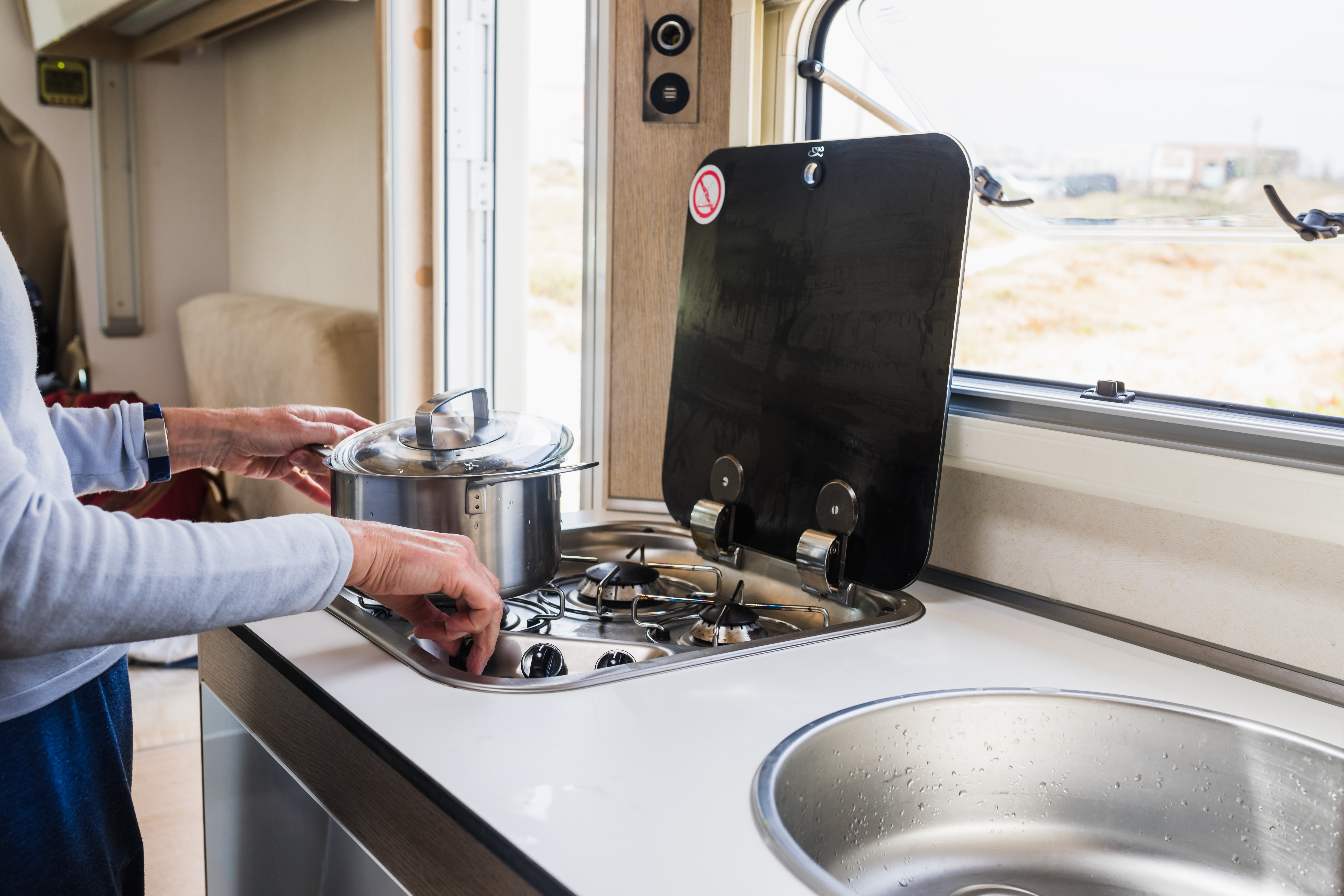 Woman cooking in a camper kitchen