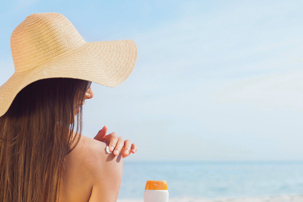 Woman applying sunscreen by the beach