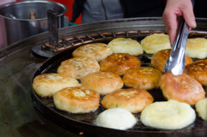 Hotteok or sweet pancakes getting cooked in a pan grill.