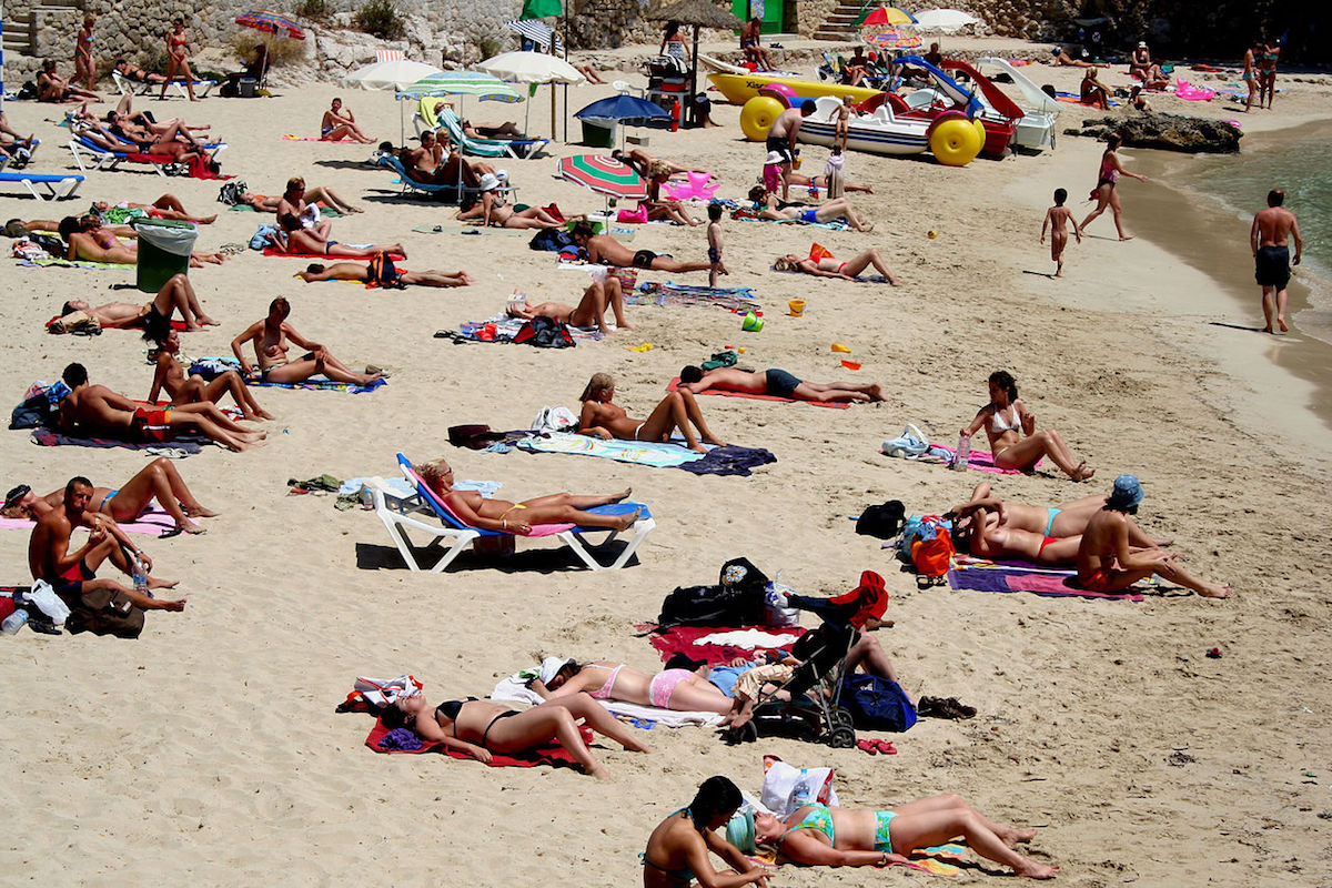 Topless women and men sunbathing on the beach