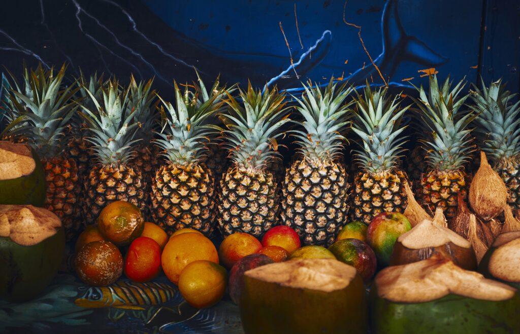 A display of assorted fruits like pineapple, orange, mango and coconut.