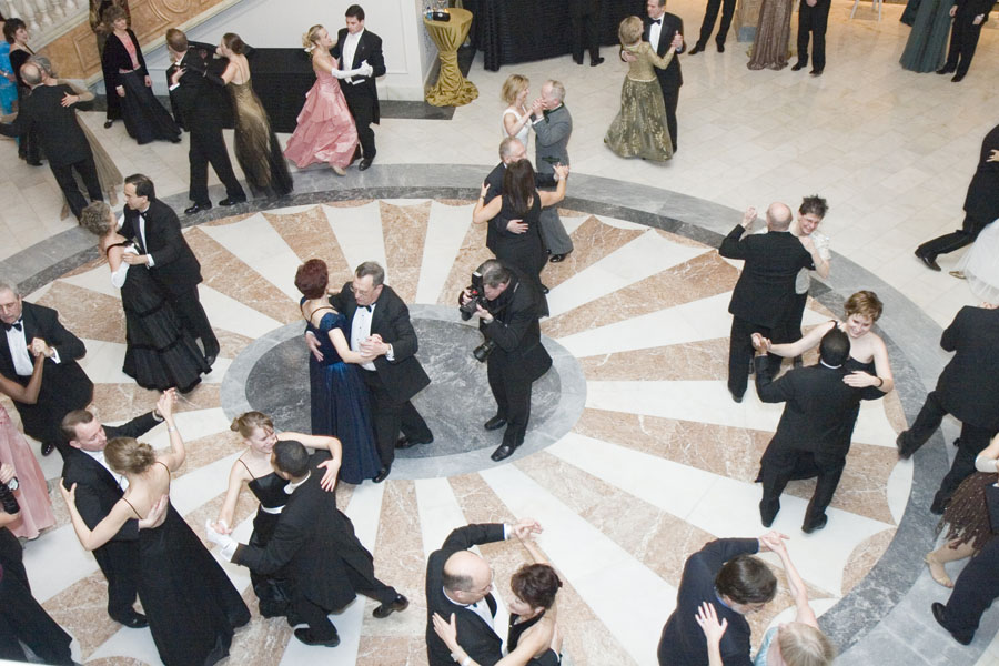People dancing waltz in a ballroom.
