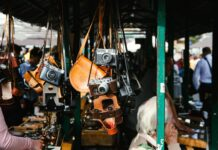 Vintage cameras and camera holders displayed in a flea market.