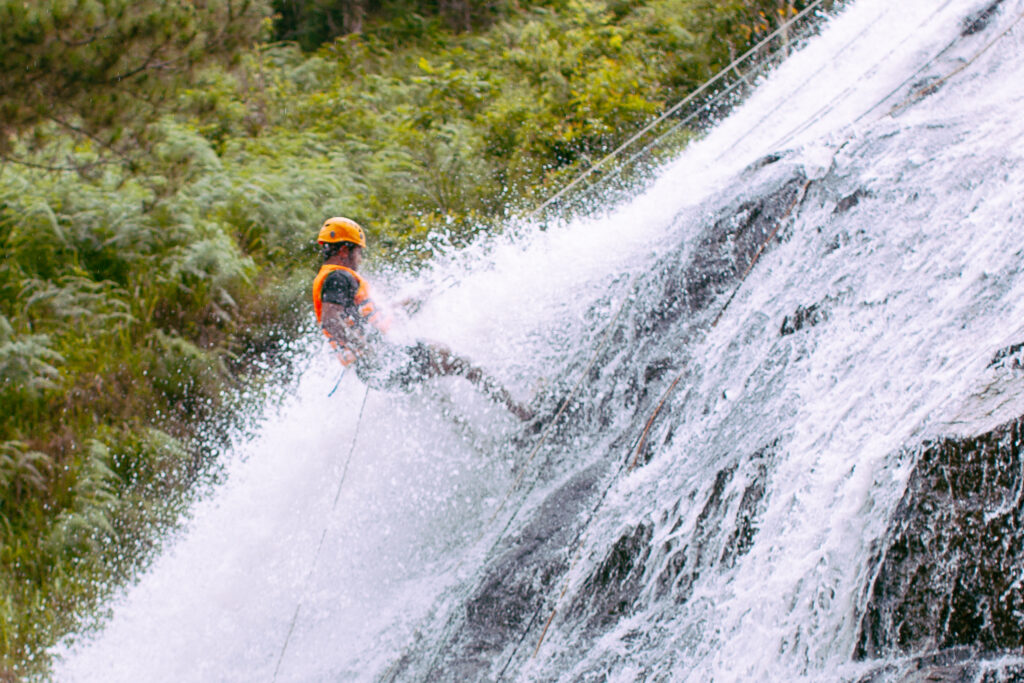 A man rappelling down a waterfall.
