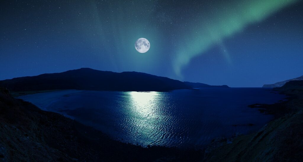 A view of northern lights and a full moon from the seashore
