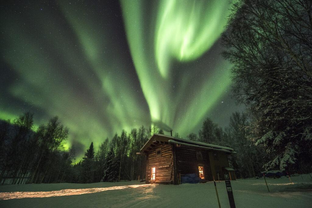 Aurora Borealis above a cabin.