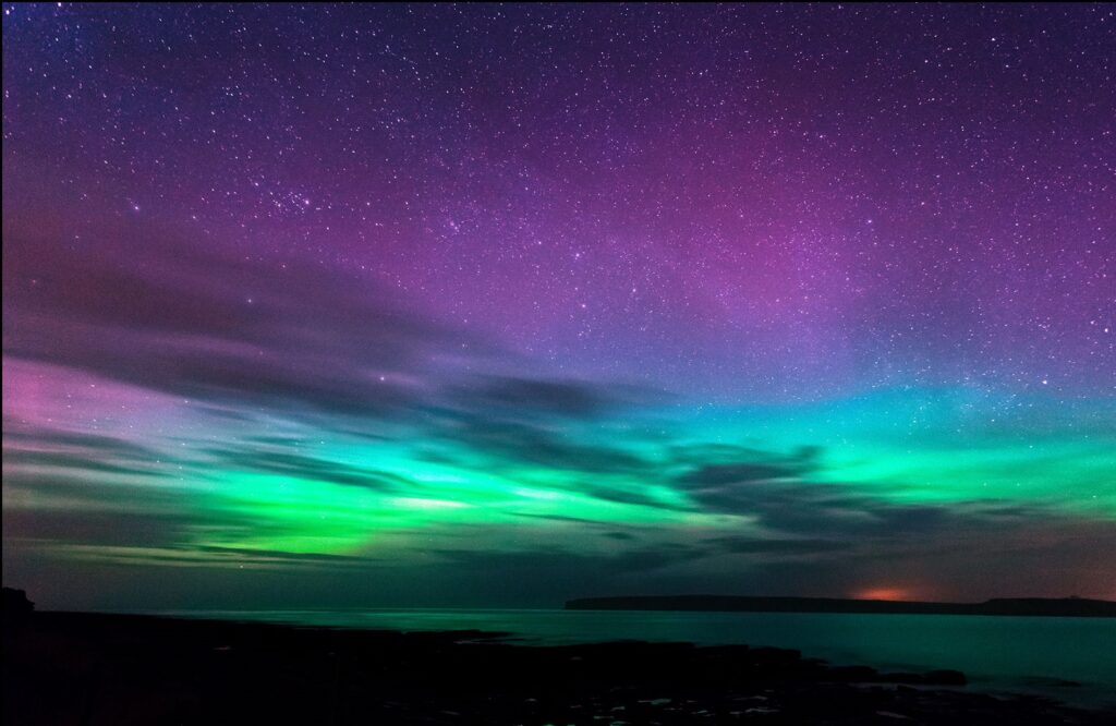 A mix of purple, blue and green northern lights above the sea.