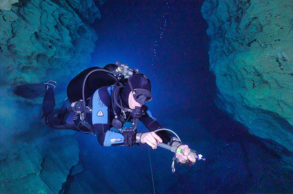 A man swims inside an underwater cavern.