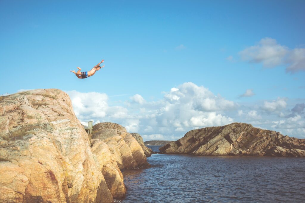 A man jumping from a cliff into the water.