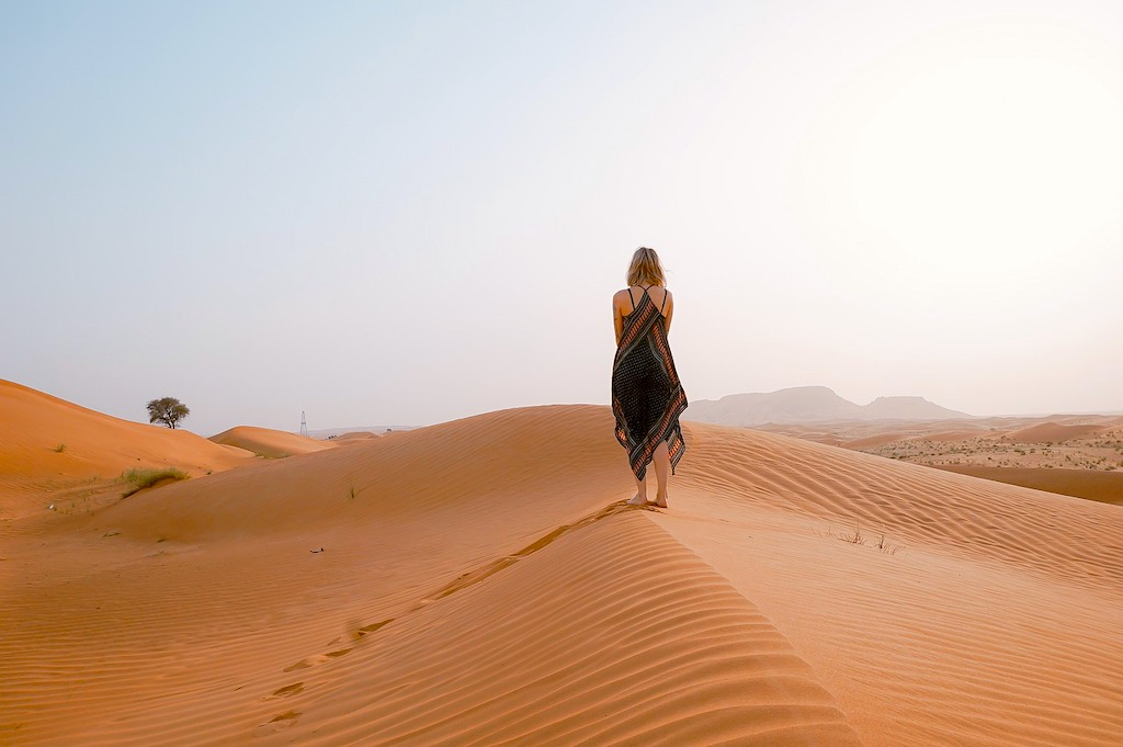 A female tourist strolling on the desert bare feet