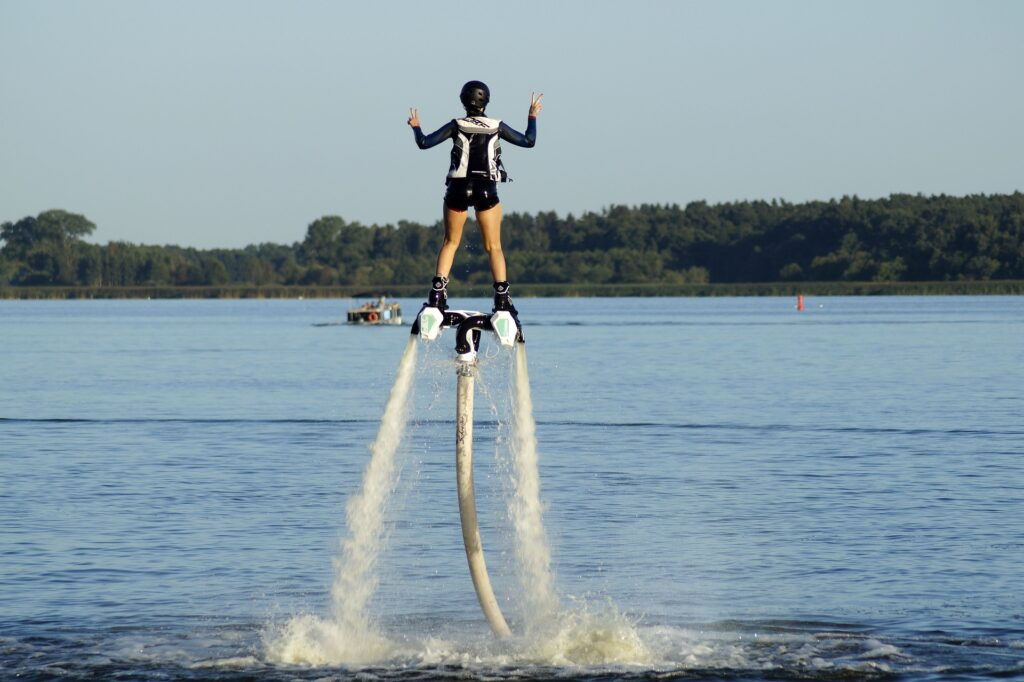 A girl riding a flyboard poses in peace sign.