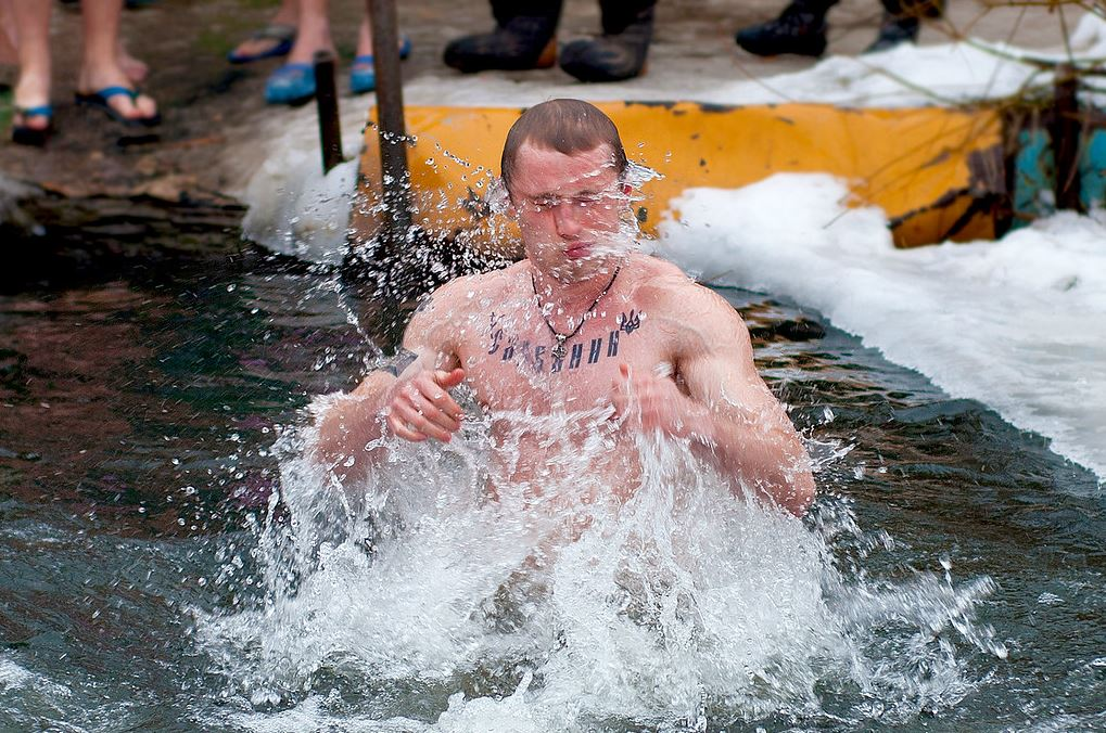 A guy splashes while swimming on an icy lake.