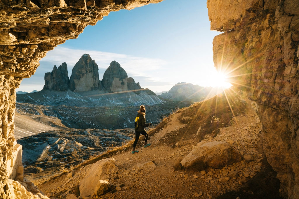 Women hiking the Italian Alps trail with hiking stick during sunrise