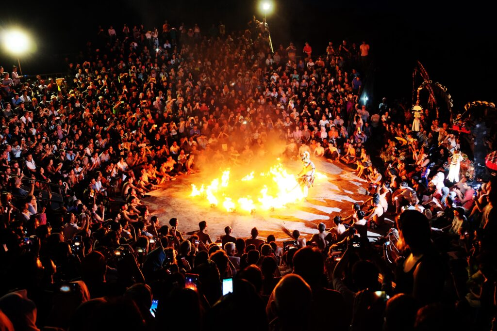 A crowd watching a fire dance performance at night.