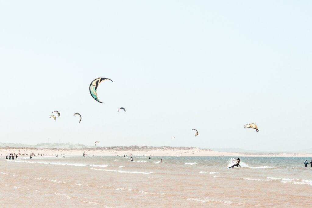 A group of people doing kite surfing near the coast.
