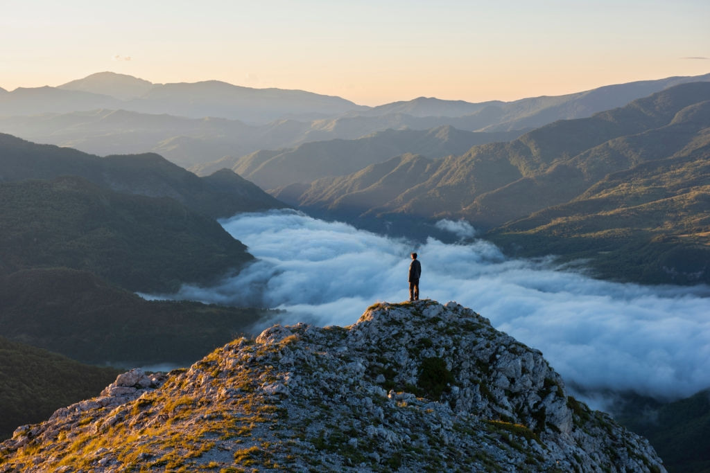 A hiker hiking the Mount Sibillini National Park during the dawn when sun starts to rise above the clouds.