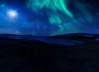 A mix of green and blue northern lights above an the waters.