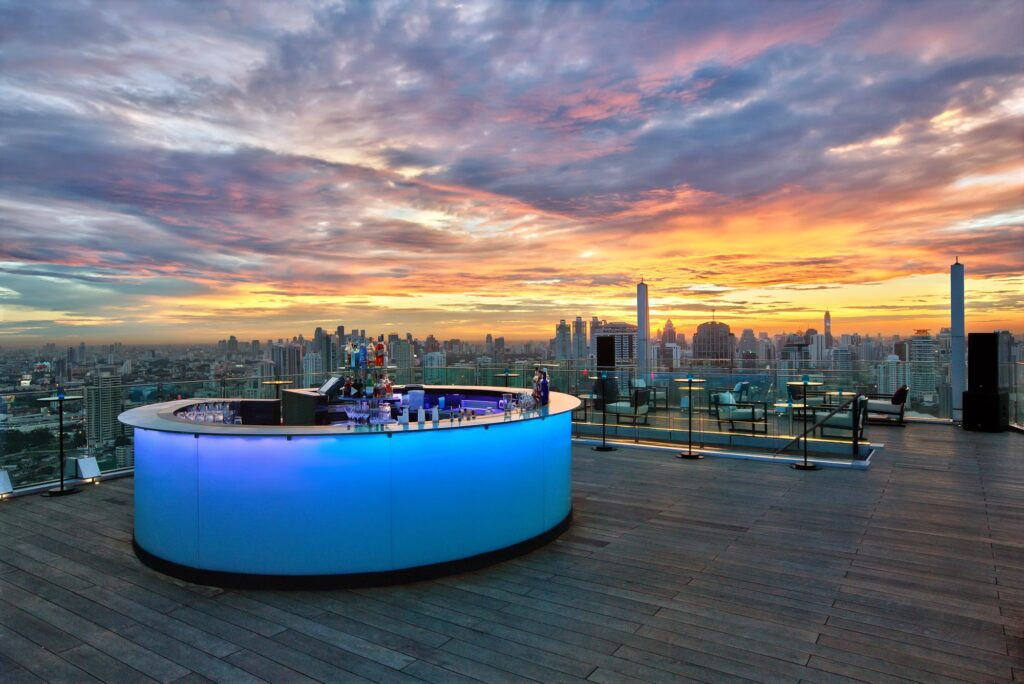 A bar balcony in a rooftop during sunset.