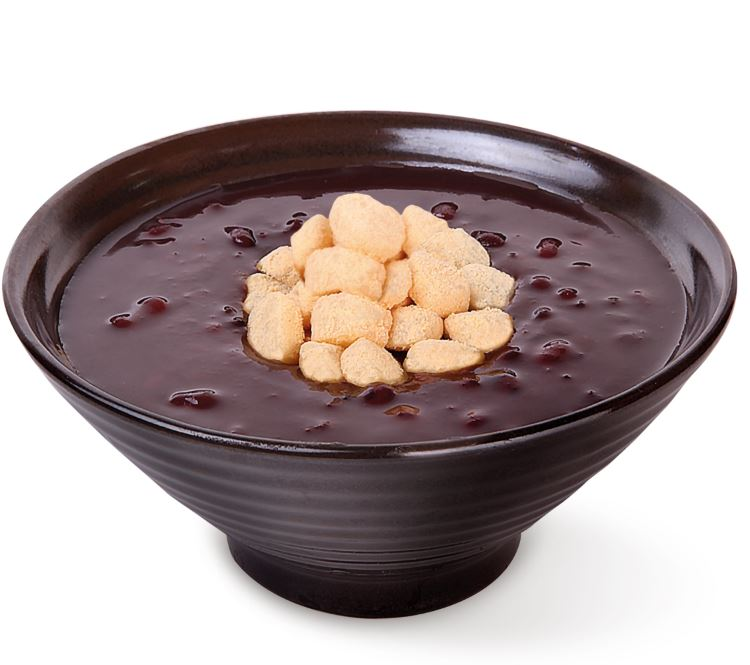 A bowl of red bean soup with rice cakes on top.
