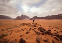 A guy traversing through the red sand desert in Jordan