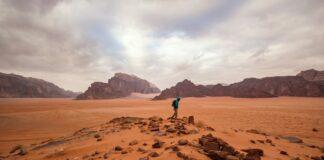A guy traversing through the red sand desert in Jordan