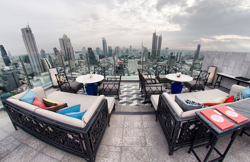 A lounge in a rooftop with two over-sized couch and cocktail tables.