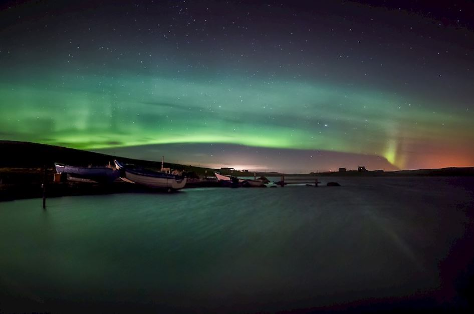 A view of the Northern lights in the horizon of a sea.