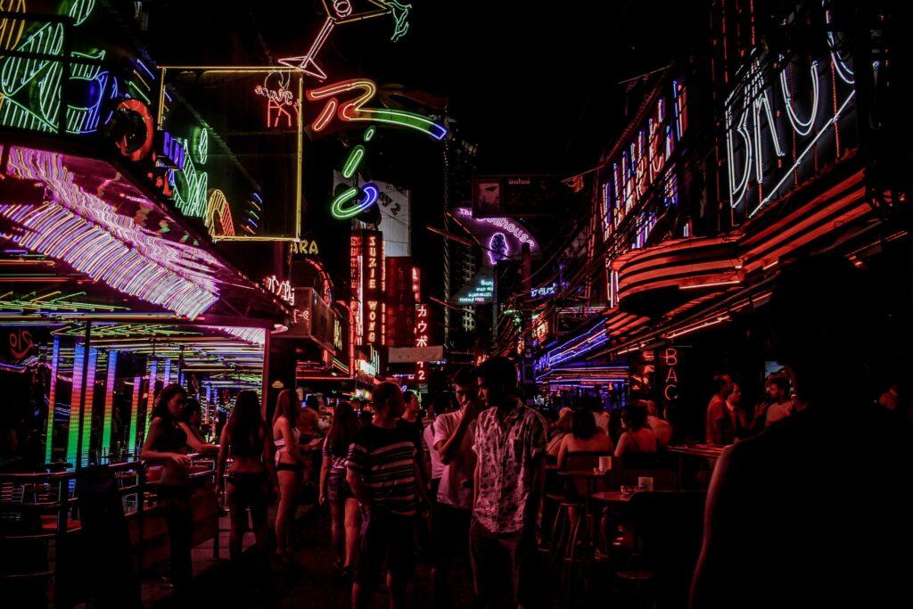 People standing between building full of lights.