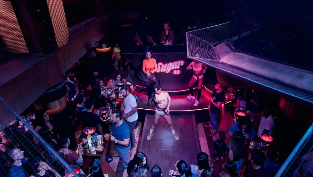 A nightclub with dancers in front of DJ booth and people drinking around.