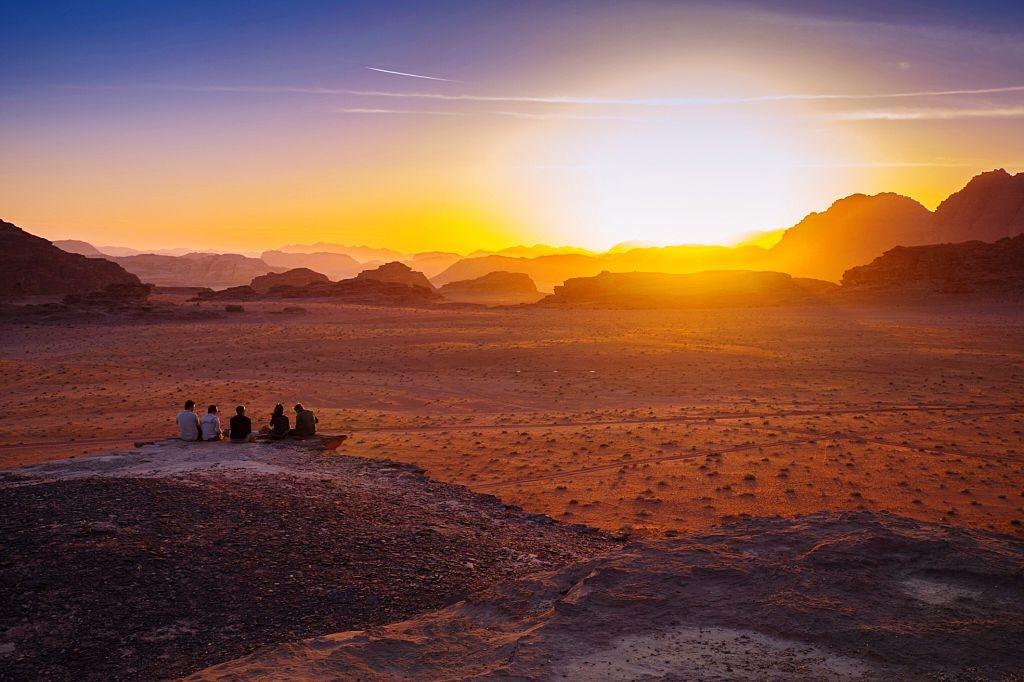 Friends enjoying sunset on a cliff in Jordan