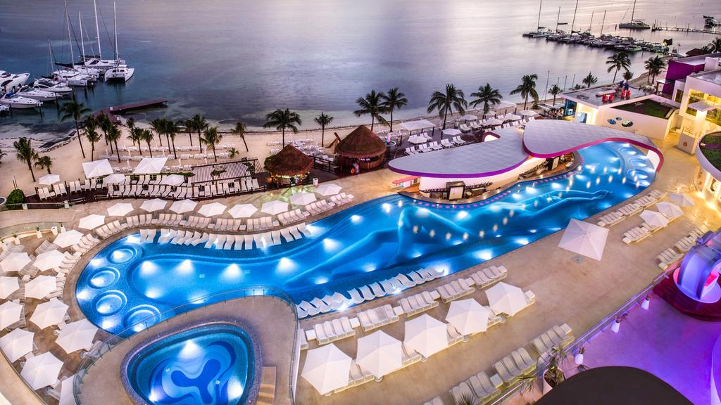 Temptation Cancun clothing optional resort with lighted pool in the evening