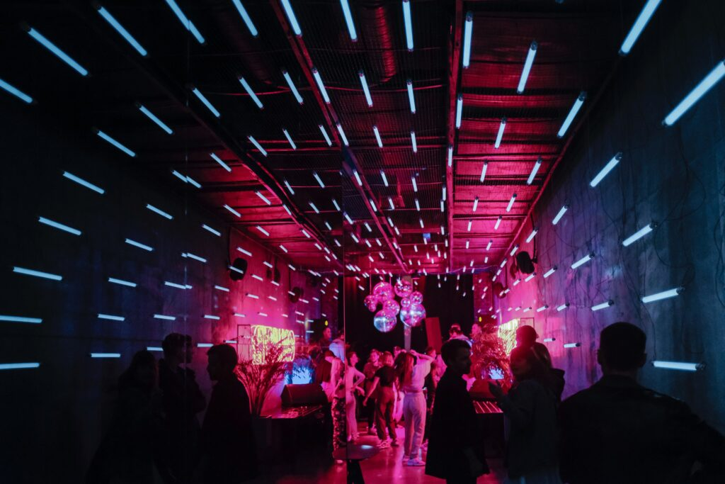 People inside a dark room with blue lights and disco balls.