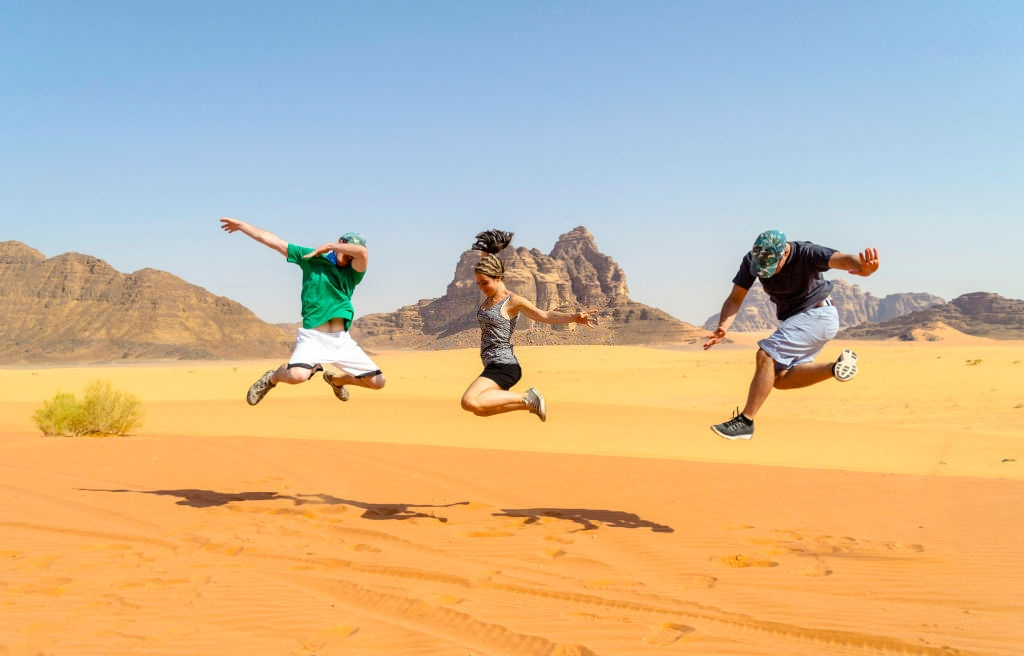 Male and female travelers doing jump posing for photo in Wadi Rum desert during the summer.