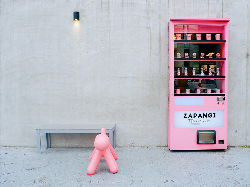 A pink vending machine beside a dog-shaped seat.