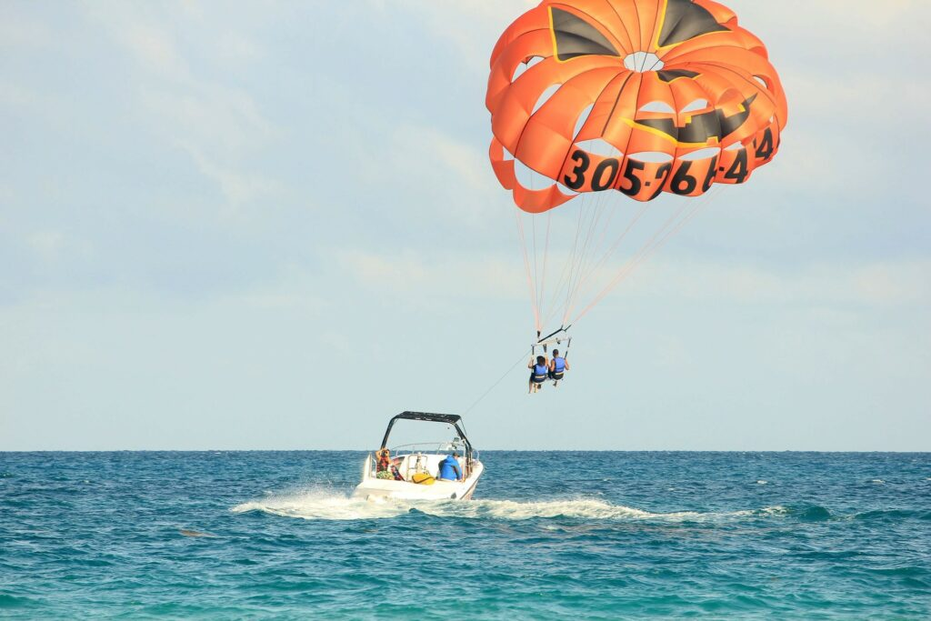 Two people riding a parachute towed by a speedboat.