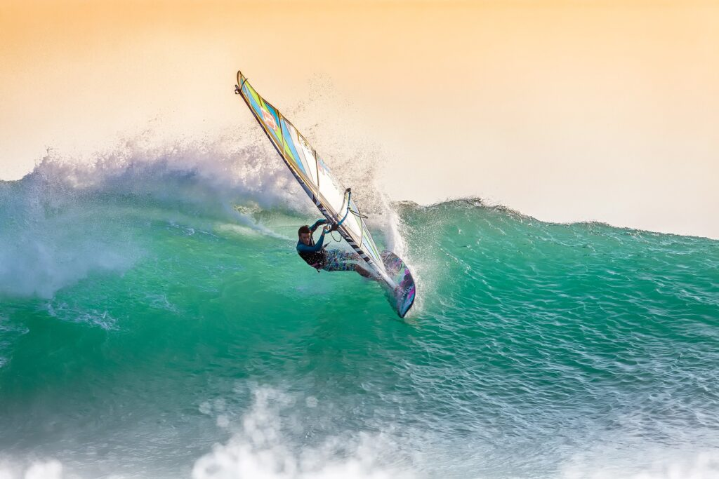 A guy doing wind surfing riding big waves.