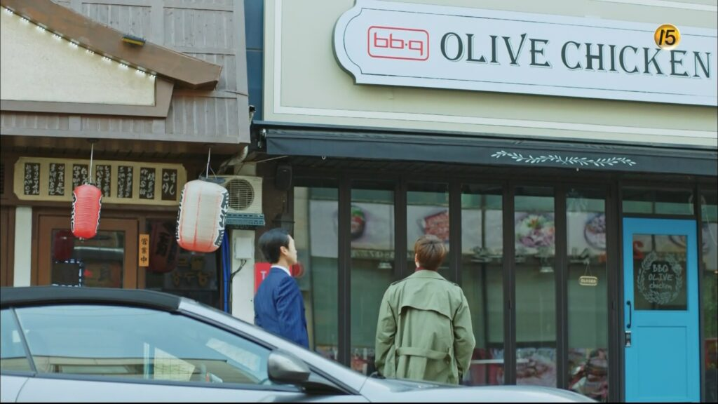 Two men outside a building with a sign that says BBQ Olive Chicken.